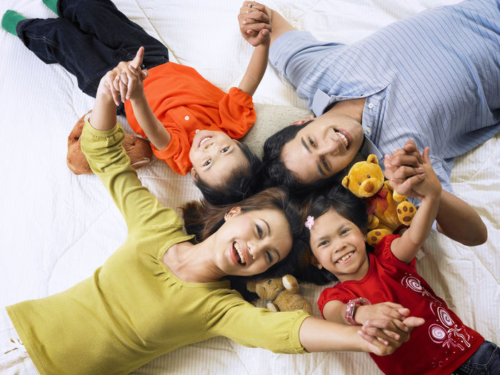 top view parent with two kids at home lying down Asian Family At Home Family Happiness Bonding Cheerful Childhood Directly Above Elementary Age Enjoyment Family Time Group Of People High Angle View Leisure Activity Looking At Camera Lying Down Lying On Back Parent With Kids Parenting Portrait Real People Simple Life Smiling Soft Toys Togetherness