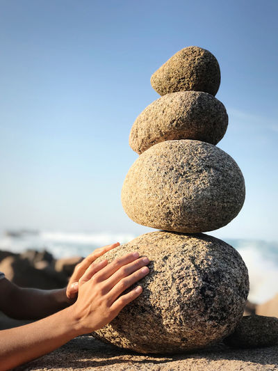 Woman hands touch vertically stacked round stones on the sea shore