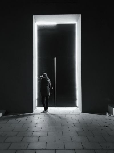 Rear view of woman standing by door at night