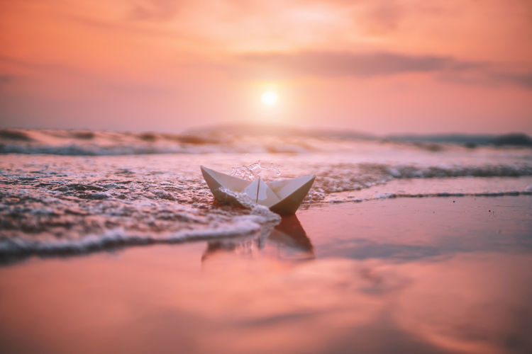Paper boat at beach against sky during sunset