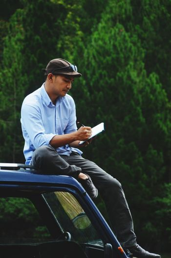 Full length of man writing on diary while sitting on car