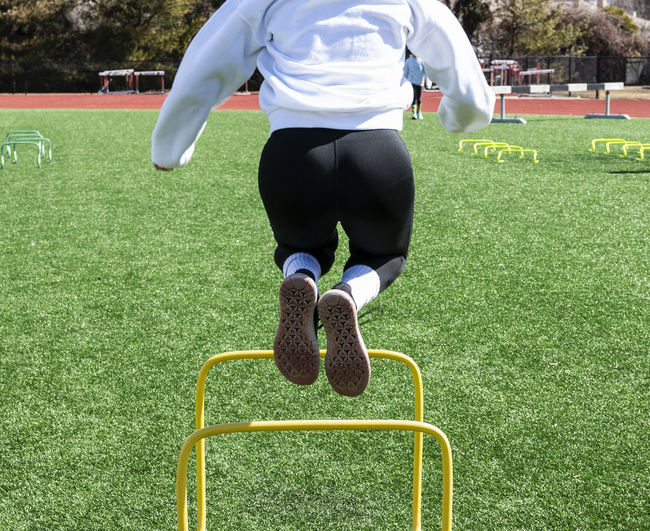 Low section of woman jumping over hurdles on turf