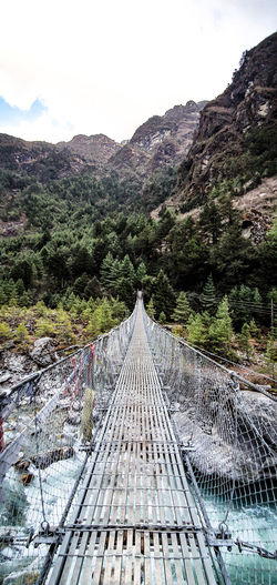 Footbridge amidst trees and mountains against sky