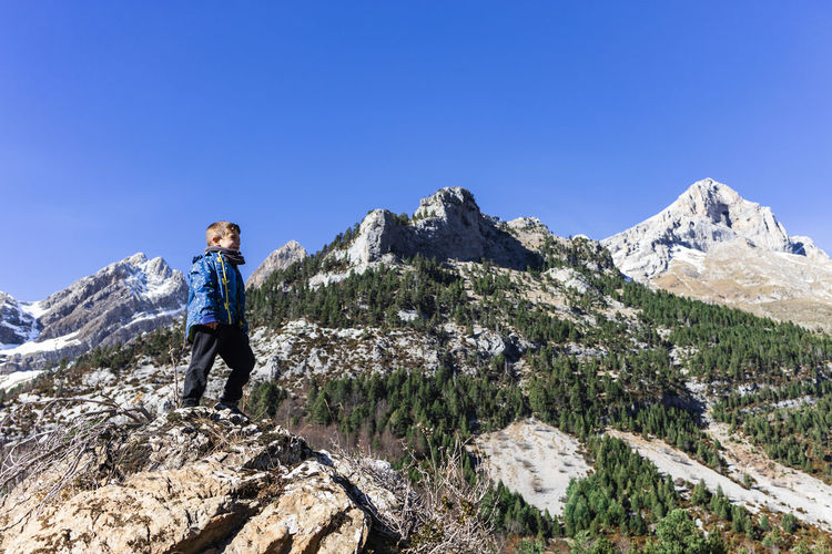 Boy standing on rock against clear blue sky