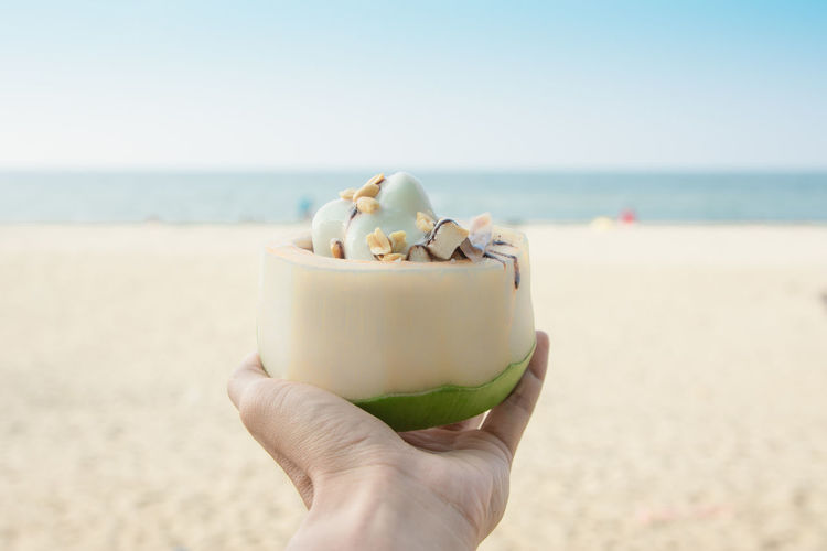 Close-up of hand holding ice cream cone on beach