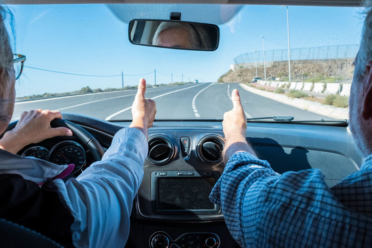 Senior couple showing thumbs up sign in car