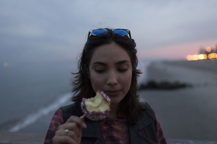 Portrait of woman eating ice cream against sky