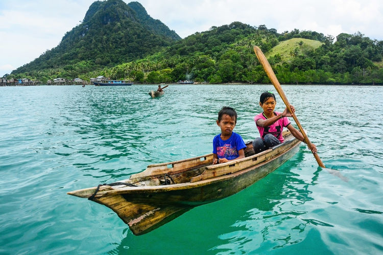 Children of The Sea Transportation Mode Of Transportation Nature Leisure Activity Lifestyles Real People Men Portrait Tree Looking At Camera Beauty In Nature Mountain Waterfront Sea Sitting Women Outdoors Sea Gypsies Children Simple Lifestyle Semporna Sabah Paddling Boat Blue Sea And Clear Water Clear Sky Summer Day Beauty In Nature