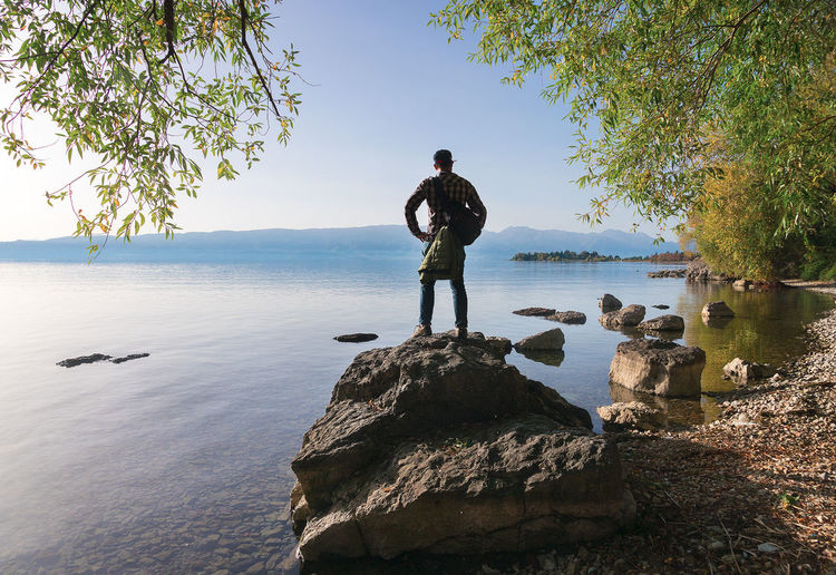 Man standing on rock by sea against clear sky