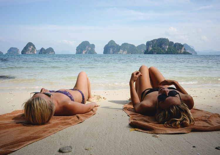 Young Women Sunbathing On Shore At Beach