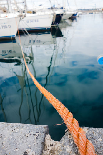 Orange rope going from the harbor to a far boat, pozzuoli harbor, bay of Naples, Italy Bay Of Naples Bay Of Naples, Italy. Blue Day Fishing Nautical Vessel Orange Outdoors Pozzuoli Rope Rope, Blue, Orange, Boat, Har Water