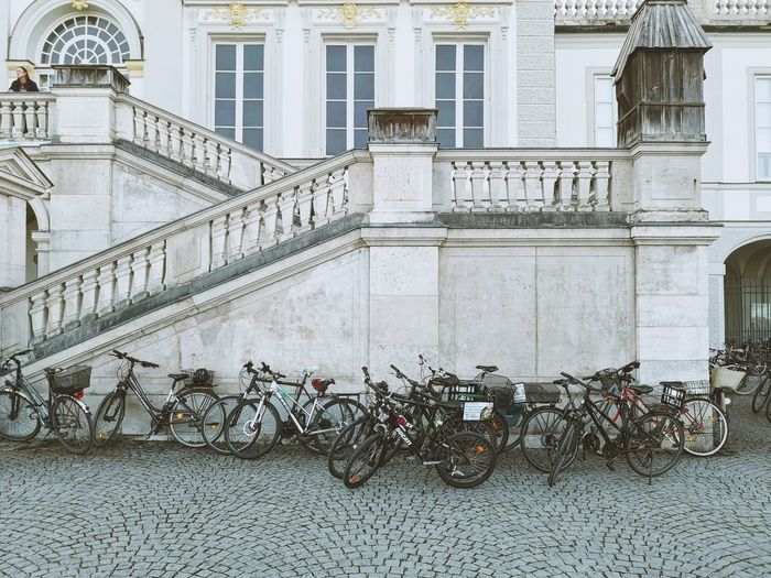 Bicycles parked on footpath by building