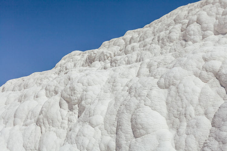 Low angle view of salt against blue sky