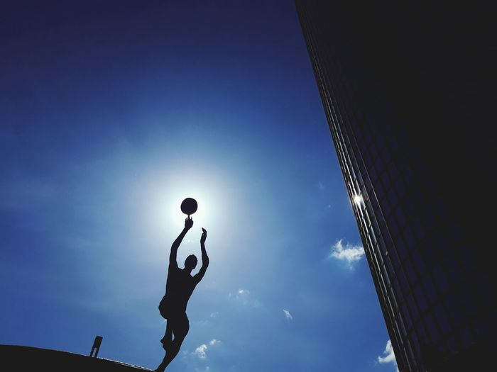 Low angle view of silhouette person against blue sky