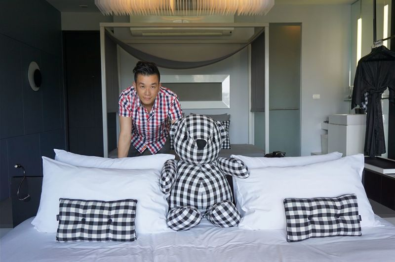 Portrait of man with checked pattern teddy bear on bed at home