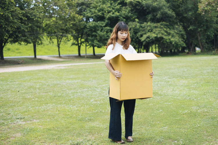 Full length of woman holding box while standing on grass against trees