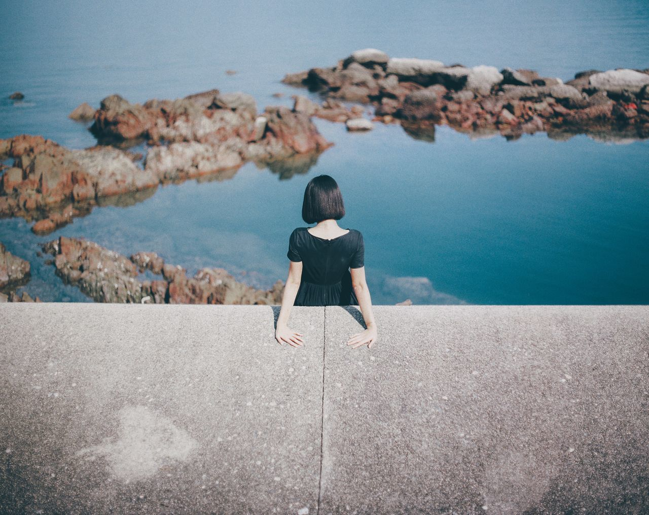 High angle view of woman standing by retaining wall against sea