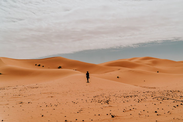 Man on sand dune in desert against sky