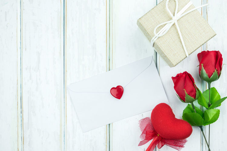 High Angle View Of Envelope With Red Roses On Table