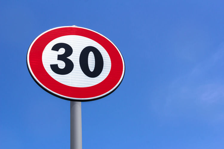 Road sign 30 Km speed limit .Traffic Limitation Order, Red Circle. Space for text. 30 Circle City European  Isolated Red Road Sign Signs Background Blue Car Concept Kilometer Km Limit Limitation Maximum Metal Number Old Pole Round Sky Space