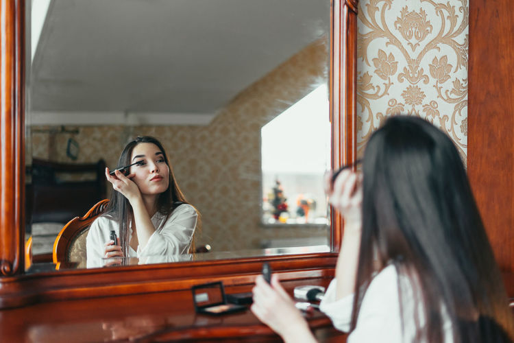 Young woman doing make-up while looking at mirror