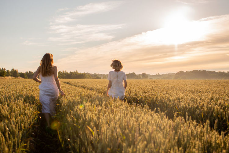 Rear view of women walking amidst plants on land against sky during sunset