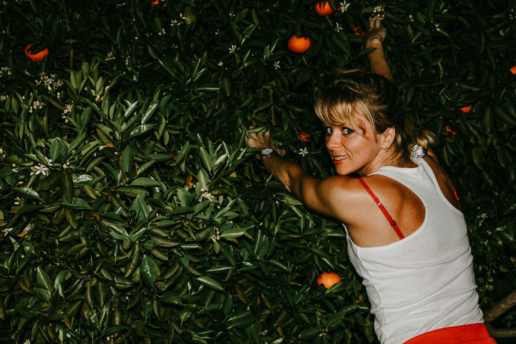 Woman standing by plants with oranges