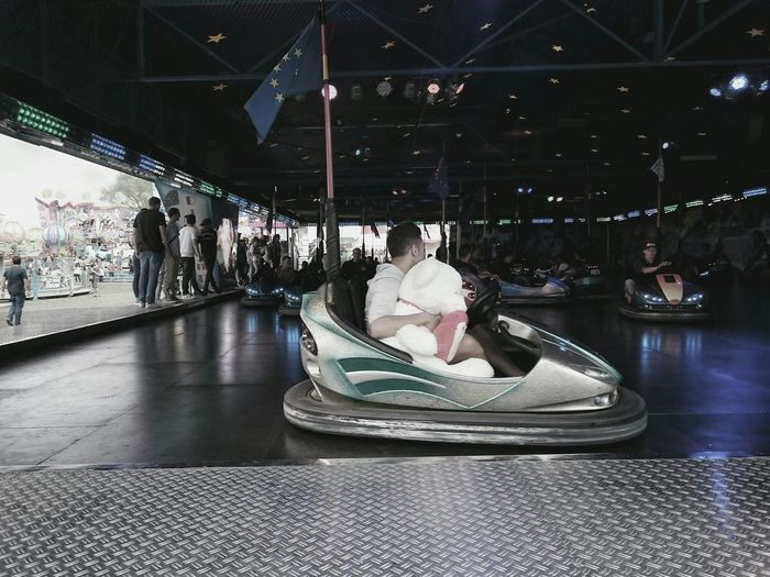People Enjoying Bumper Car Ride In Amusement Park