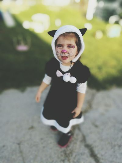 Portrait of girl with cat make-up and costume standing on footpath