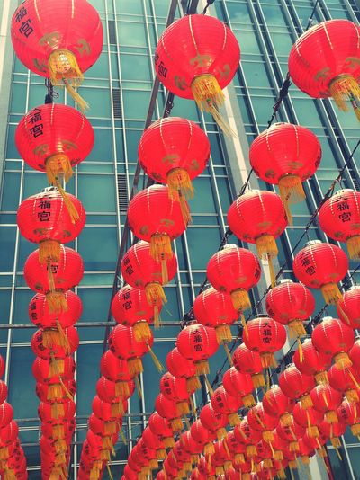 Low angle view of chinese lanterns hanging against building on sunny day