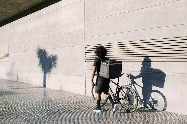 Rear view of man riding bicycle against wall