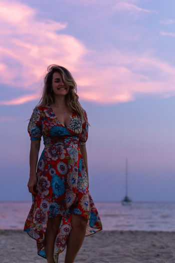 Young woman standing at beach against sky during sunset