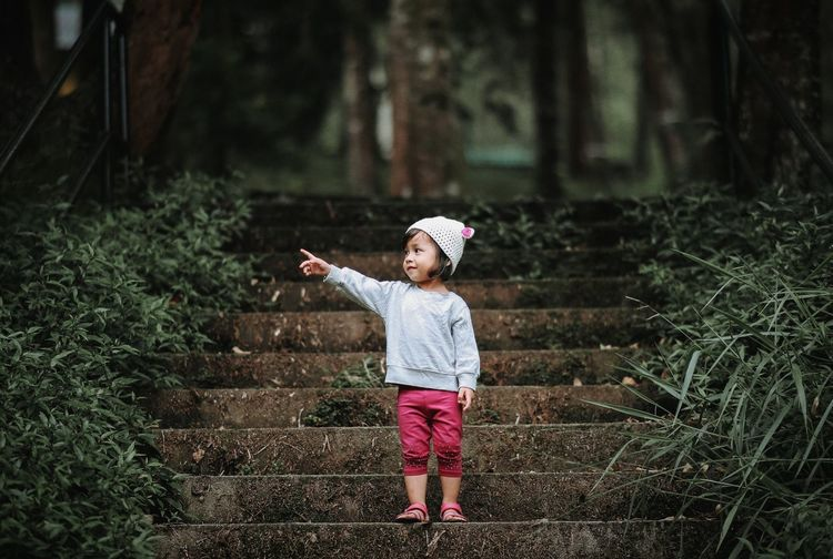 Full length of girl gesturing while standing on steps in forest