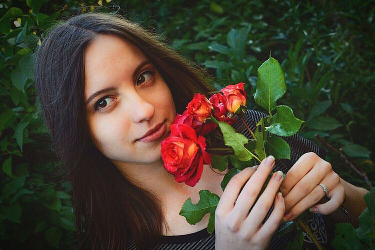Thoughtful Young Woman Holding Red Roses