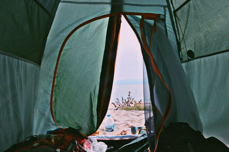 Tent on table by sea against sky
