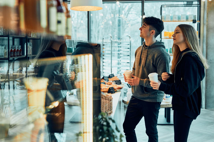 Friends doing shopping in a coffee shop.. people buying coffee and sweet snacks to go