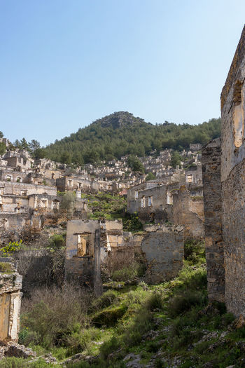 The abandoned hillside village of Kayakoy in Turkey. A left over from the Greco-turkish disagreements. Ancient Ancient Civilization Architecture Building Building Exterior Built Structure Clear Sky Copy Space Day Empty History Kayakoy Land Mountain Nature No People Old Old Ruin Outdoors Plant Sky The Past Tree