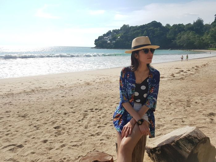 Woman wearing hat while sitting at beach against sky