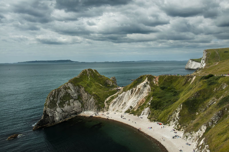 Mossy mountains by sea against cloudy sky at durdle door