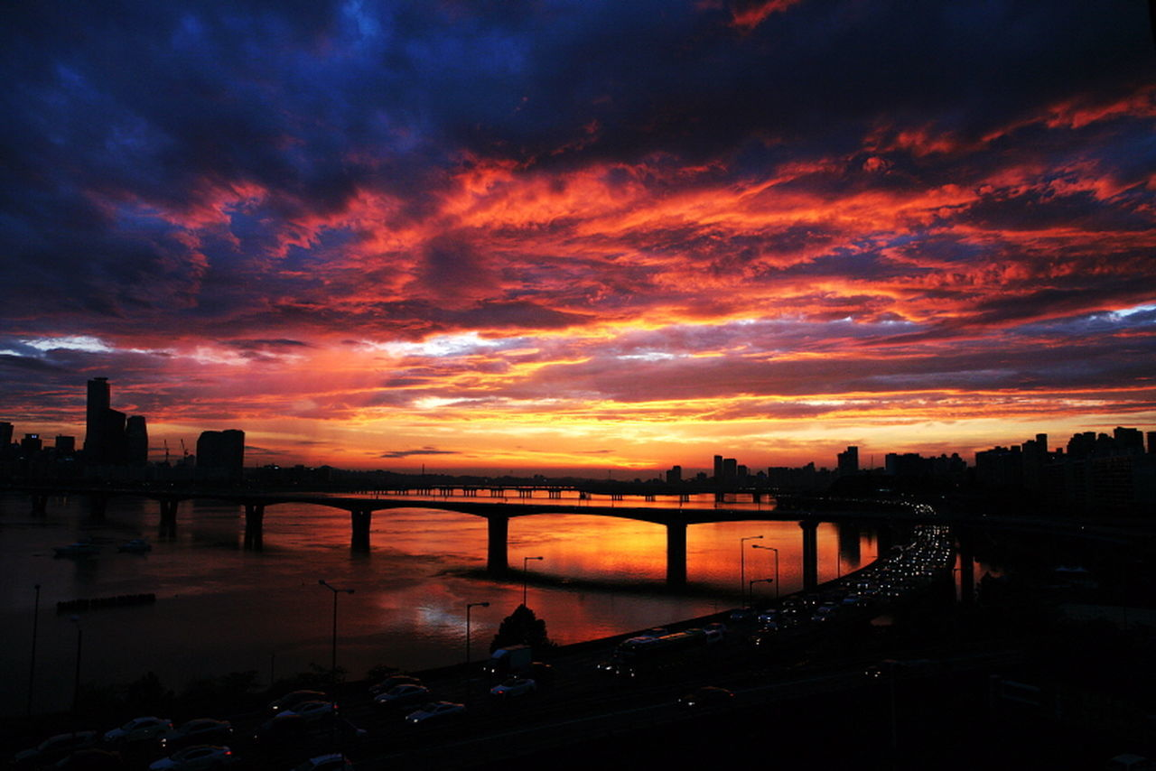 sunset, built structure, sky, architecture, cloud - sky, bridge - man made structure, orange color, silhouette, building exterior, water, river, connection, outdoors, transportation, nature, beauty in nature, city, travel destinations, scenics, no people, cityscape, day