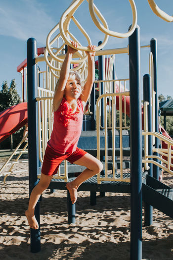 Full length of girl hanging on monkey bars at playground