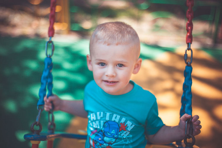 Portrait of smiling boy sitting on swing at playground