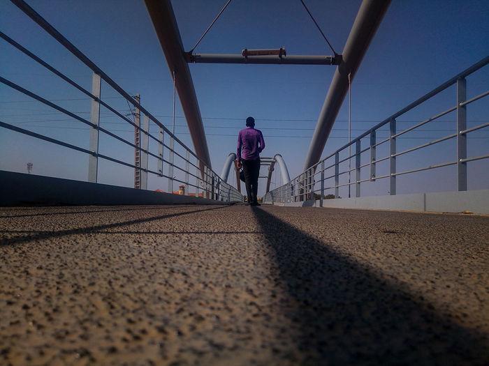 Surface level shot of man walking on bridge against clear sky