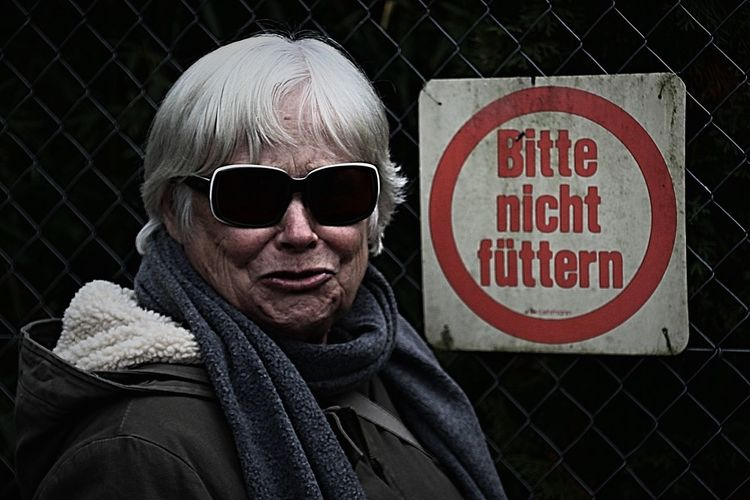 Close-up portrait of senior woman wearing warm clothing by chainlink fence