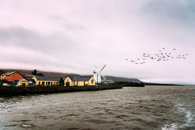 Flock of birds over windmill in the coast of Ireland , Irish, Sea Wild Atlantic Way Windmill Animal Themes Architecture Beauty In Nature Bird Building Exterior Built Structure Cloud - Sky Flock Of Birds Flying Nature No People Ocean Outdoors Ring Of Kerry Sky Water Waterfront