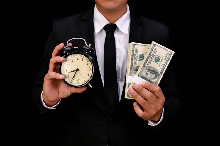 Midsection of businessman holding currency and clock against black background