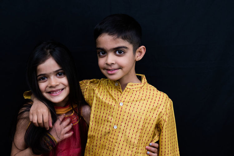Portrait of smiling siblings against black background
