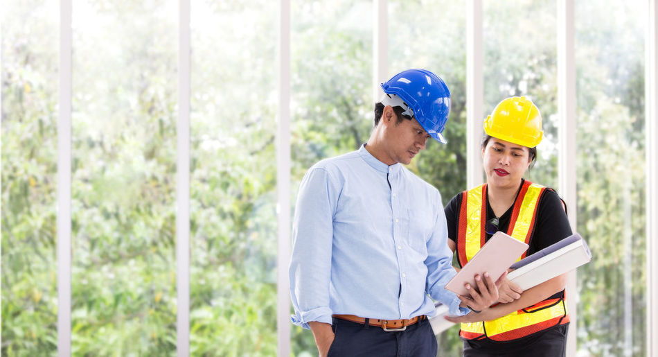 Business people wearing hard hats discussing over digital tablet in office