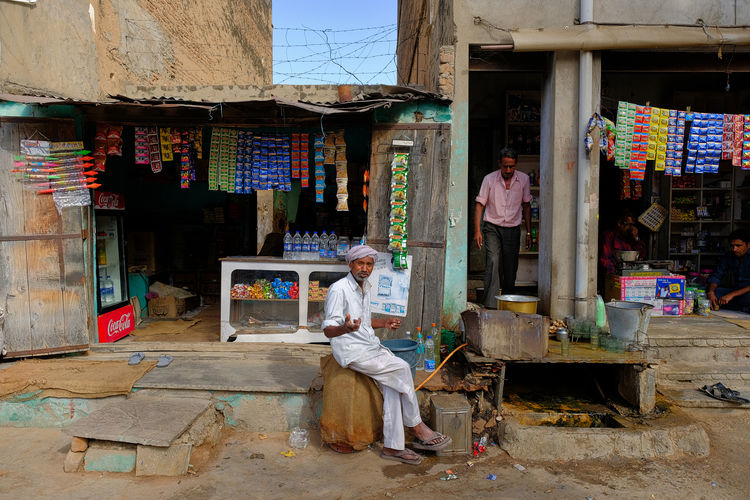 Daily life of street market in Mandawa, India. Historical Building Old Town Adult Architecture Business Casual Clothing Day Full Length Historical Lifestyles Mandawa Market Men Occupation People Real People Retail  Sitting Small Business Standing Store Women Working
