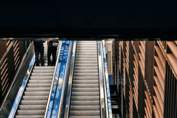 Low angle view of people walking on escalator